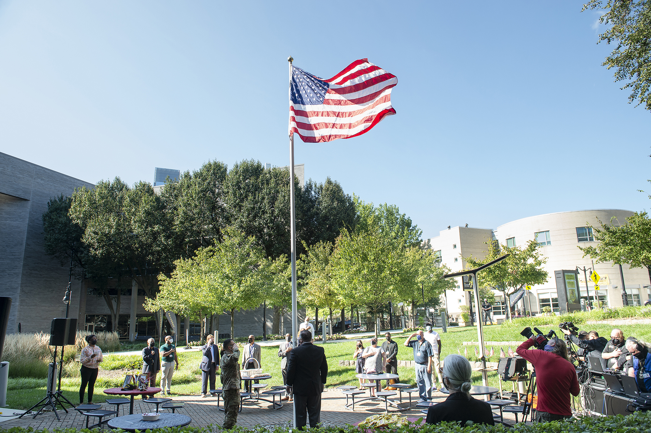 Students staff and faculty gathered in a circle around the American Flag
