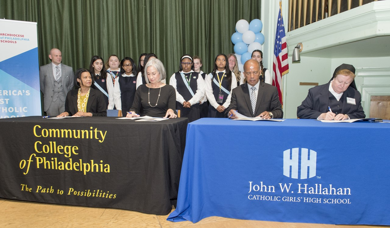 Academic leaders from Community College of Philadelphia and John W. Hallahan Catholic Girls' High School signing the paperwork for a new, dual-enrollment partnership on May 9.