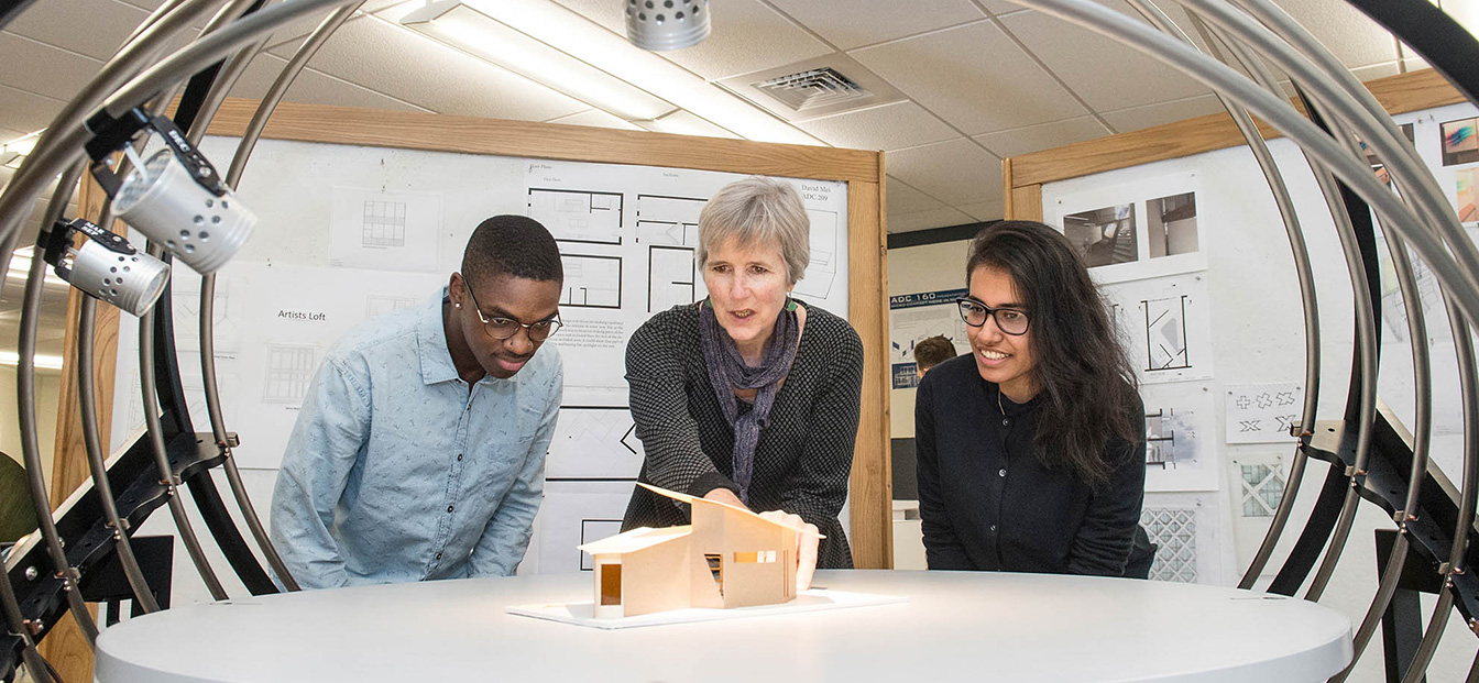 Professor working with 2 students around an architectural model