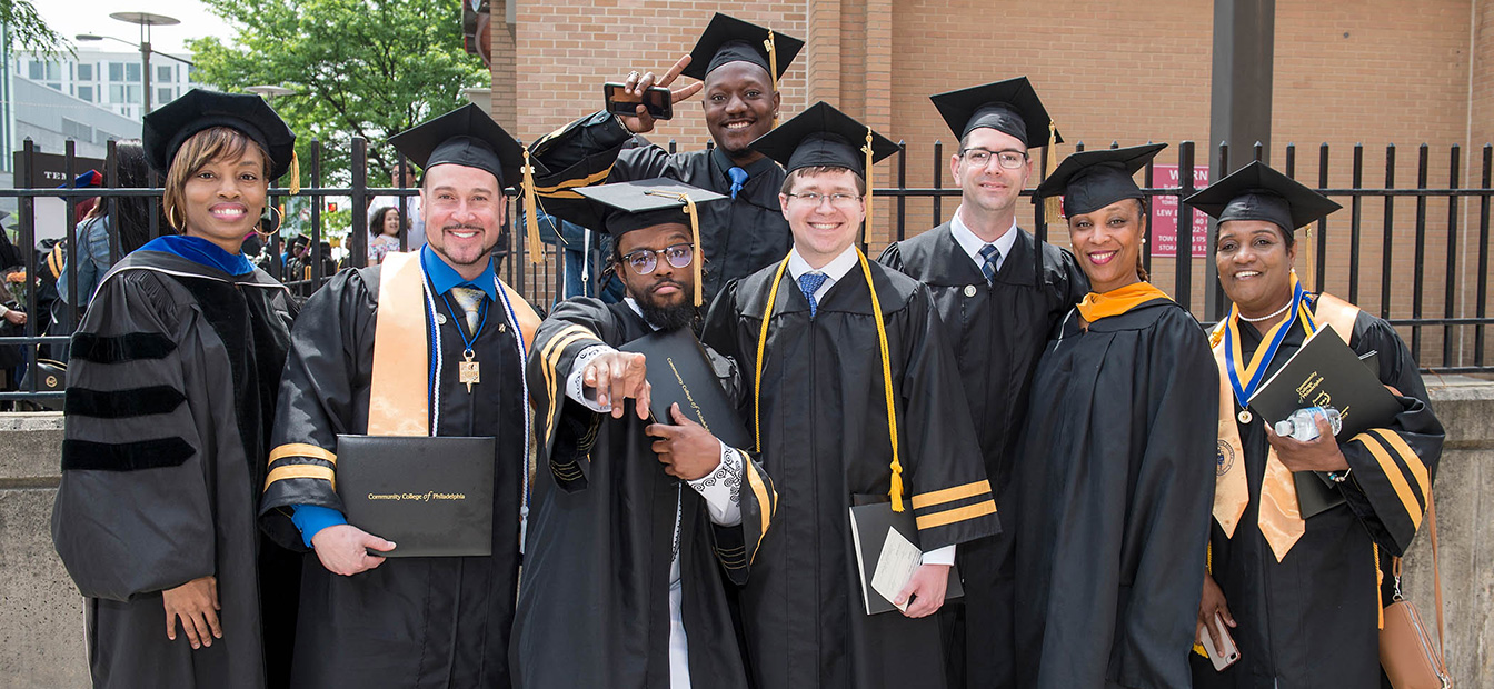 group of graduates in gowns smiling at camera