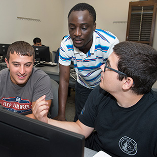 3 students around a computer work station