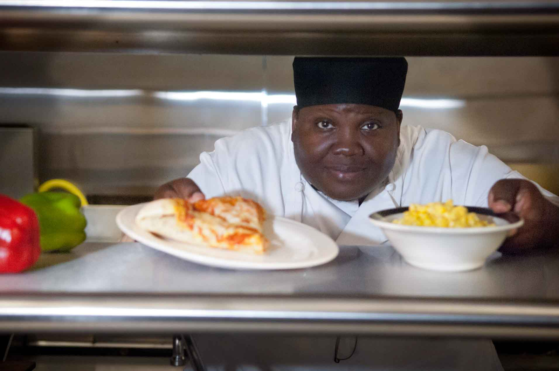 A woman in chef's clothing placing pizza and corn on a counter.