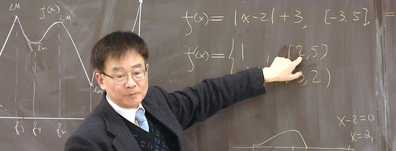 Professor teaching mathematics on chalkboard at Community College of Philadelphia.