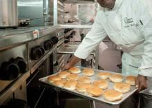 CCP student taking out baked goods from oven in kitchen.