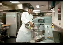 CCP student using the mixer in kitchen.