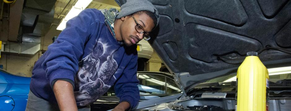 Student in Automotive Program working on a car in CCP garage.